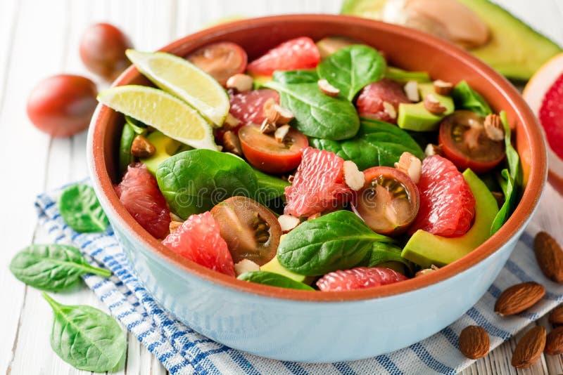 新鲜的沙拉用菠菜、鲕梨、蕃茄、葡萄柚和杏仁在白色木背景 免版税库存图片