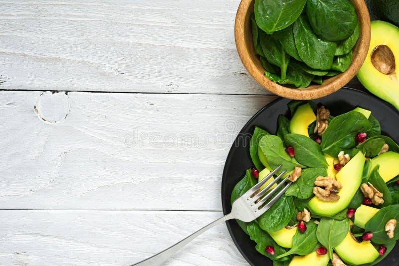 新鲜的沙拉用鲕梨、菠菜、石榴和核桃在黑色的盘子有叉子的 健康的食物 免版税库存图片