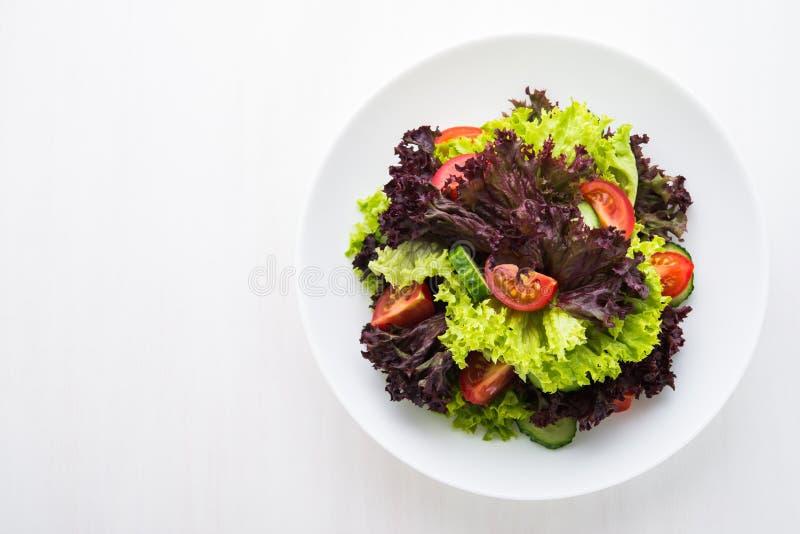 新鲜的沙拉用绿色和紫色莴苣、蕃茄和黄瓜在白色木背景顶视图 库存照片