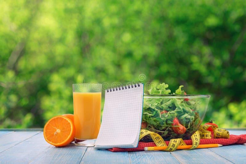 新鲜的沙拉,橙汁,有一个空的笔记本的测量的磁带 免版税图库摄影