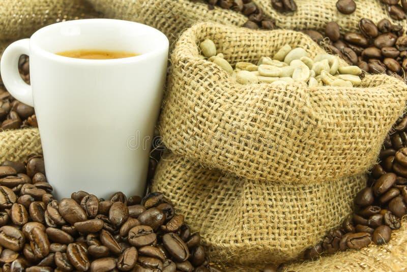 新鲜的浓咖啡和绿色咖啡豆在小黄麻请求 库存图片