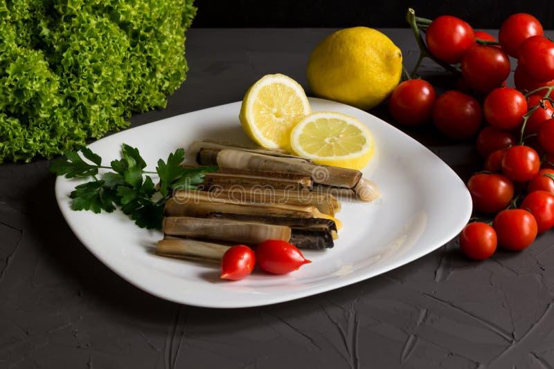 新鲜的海鲜用荷兰芹和柠檬、沙拉和蕃茄,意大利烹调,在一块白色板材的地中海食物 免版税库存照片