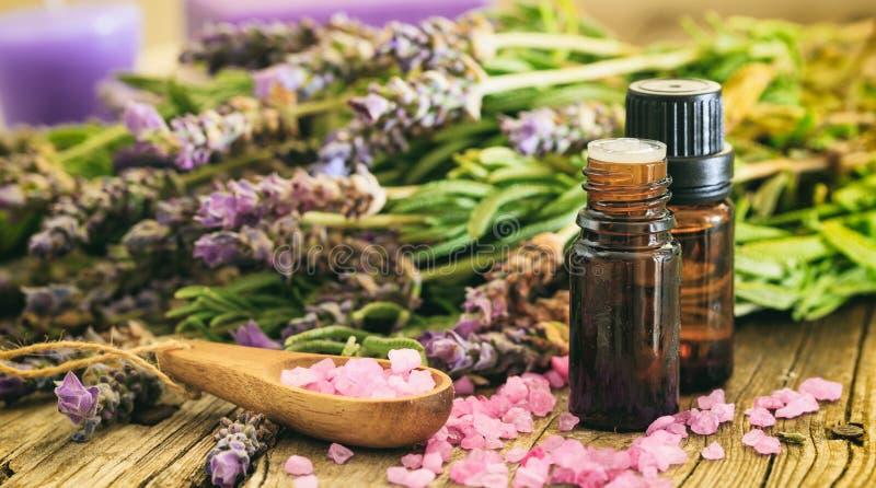 新鲜的淡紫色、精油和腌制槽用食盐在木背景 免版税库存图片