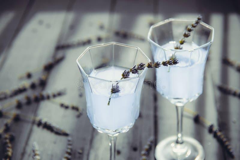 新鲜的淡紫色柠檬水的关闭与在美丽的玻璃的花在后面光的黑暗的木桌上 E r 免版税库存照片