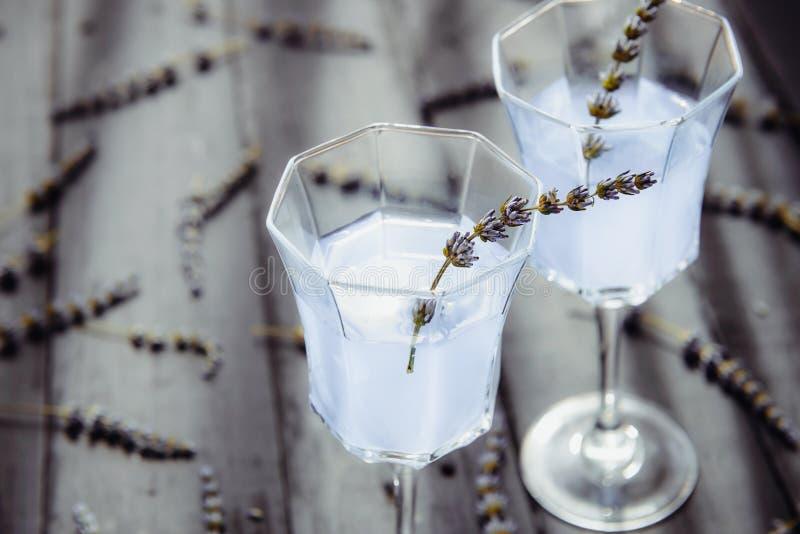 新鲜的淡紫色柠檬水的关闭与在美丽的玻璃的花在后面光的黑暗的木桌上 E r 图库摄影