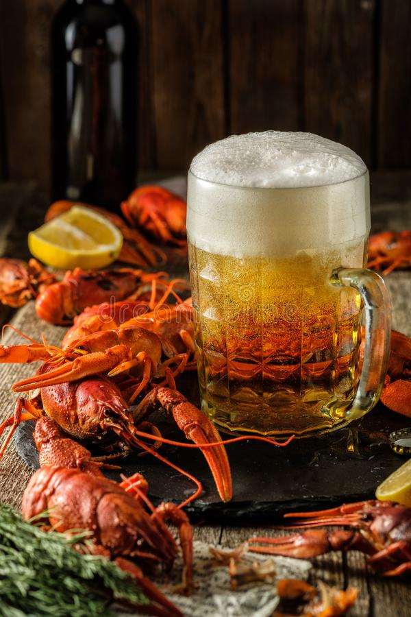 新鲜的煮沸的小龙虾和一个杯子在一张木桌上的啤酒 库存照片