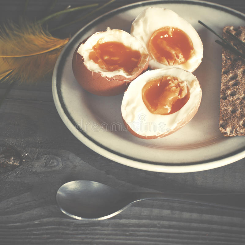 新鲜的煮沸的鸡蛋和绿色春天葱在板材在木tabl 免版税图库摄影