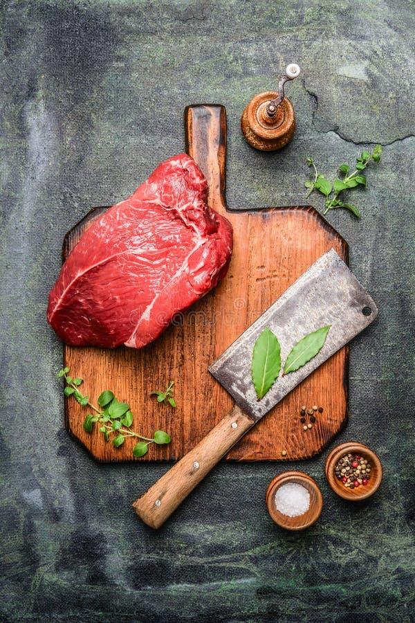 新鲜的牛肉肉片断在砧板的有大和晒干在土气背景的切肉刀的 库存图片