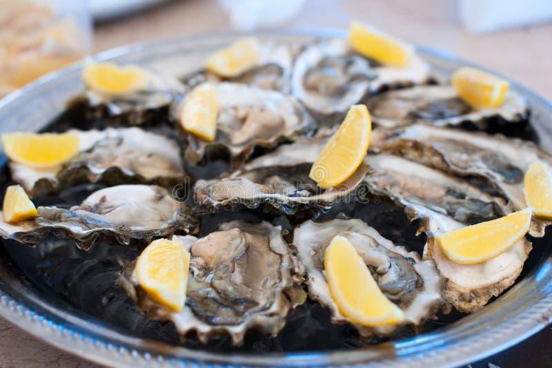 新鲜的牡蛎在冰和柠檬盘子说谎  免版税库存图片