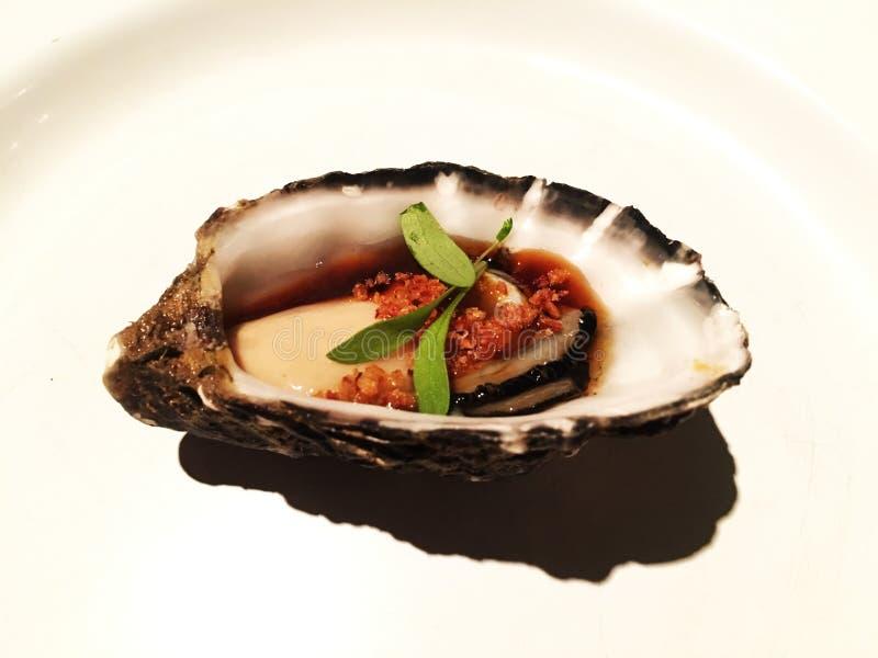 新鲜的牡蛎片断在一块白色板材的用大豆Yuzu调味汁和大蒜 图库摄影