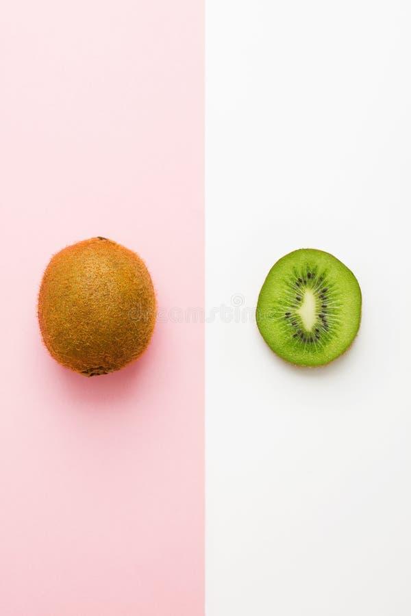 新鲜的猕猴桃整个果子和切片在桃红色白色背景 免版税库存图片