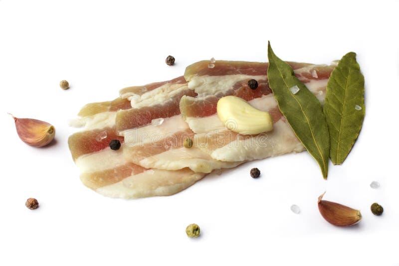 新鲜的猪肉猪油用在白色背景的香料 切的烟肉 免版税库存照片