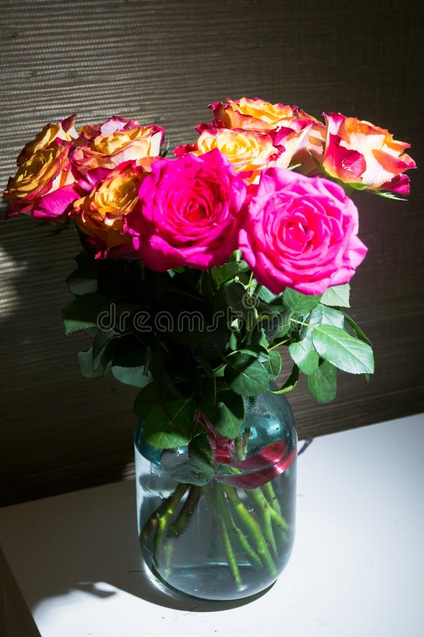 新鲜的玫瑰欢乐花束与原始的黄色和绯红色着色的在玻璃瓶子 图库摄影