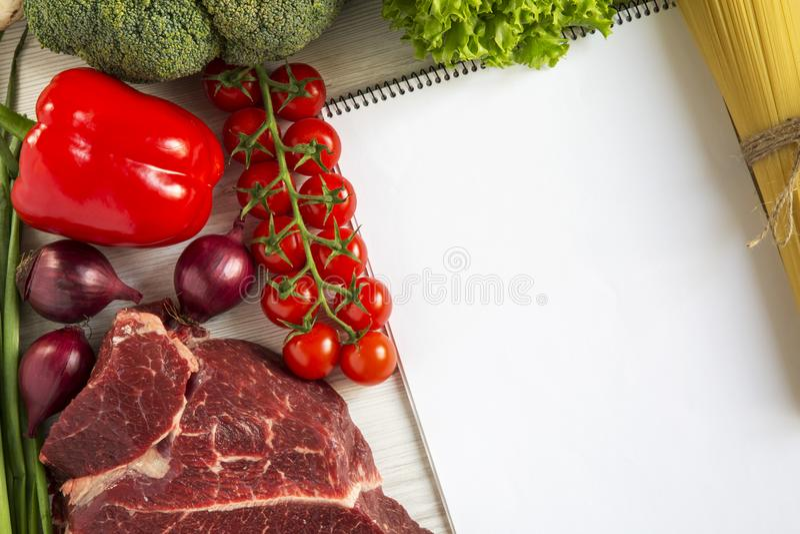 新鲜的生肉牛排用胡椒,西红柿,意大利意粉,健康食品,顶视图 库存图片