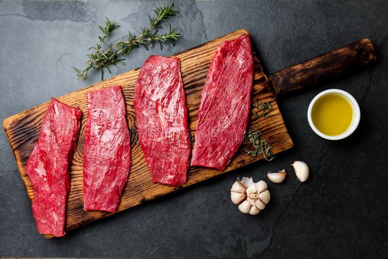 新鲜的生肉牛排 在木板,香料,草本,在蓝灰色的背景的油的牛里脊肉 烹调背景的食物 库存照片
