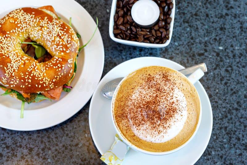 新鲜的百吉卷用沙拉和smodel钓鱼三文鱼和咖啡 早餐在咖啡馆或餐馆 免版税图库摄影