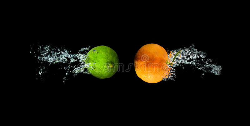 新鲜的石灰和桔子在水中与气泡浇灌飞溅iso 库存照片