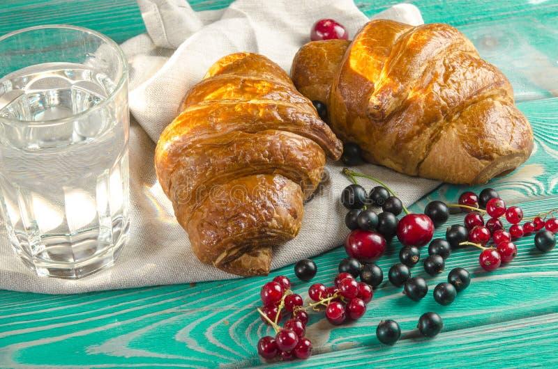 新鲜的红润新月形面包用莓果在一张木桌上说谎在新鲜的黑醋栗莓果,红浆果,樱桃旁边 库存图片