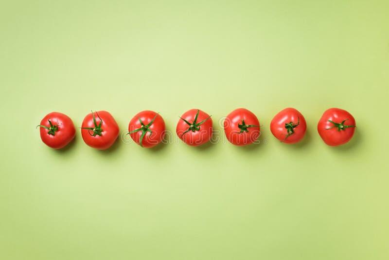 新鲜的红色蕃茄行在绿色背景的 顶视图 复制空间 最小的设计 素食主义者,素食主义者,有机食品和 库存照片