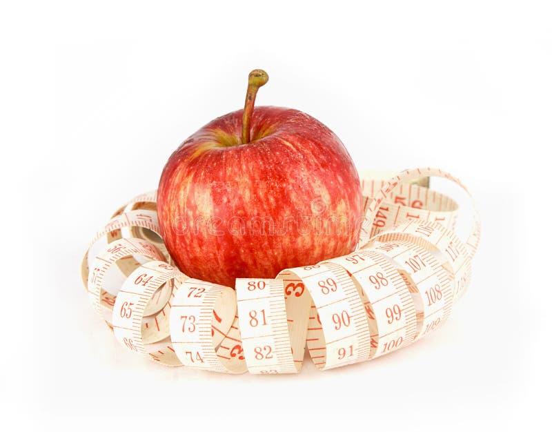 新鲜的红色水多的苹果结果实并且测量在白色backgr的磁带 库存照片