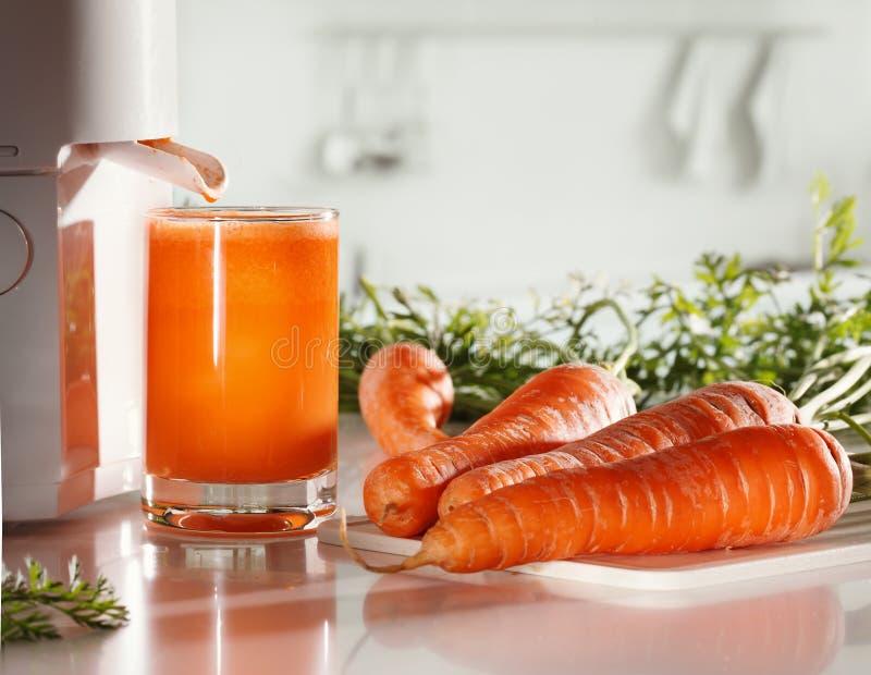 新鲜的红萝卜汁和榨汁器 免版税库存照片