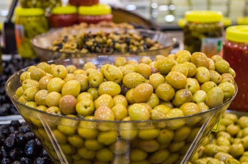 新鲜的绿橄榄待售在地方市场上 图库摄影