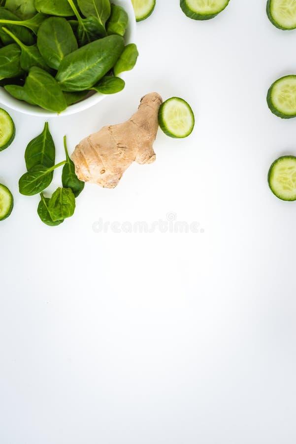 新鲜的绿色叶子菠菜、在白色背景隔绝的切片黄瓜和姜 在图象边界的菜  库存照片