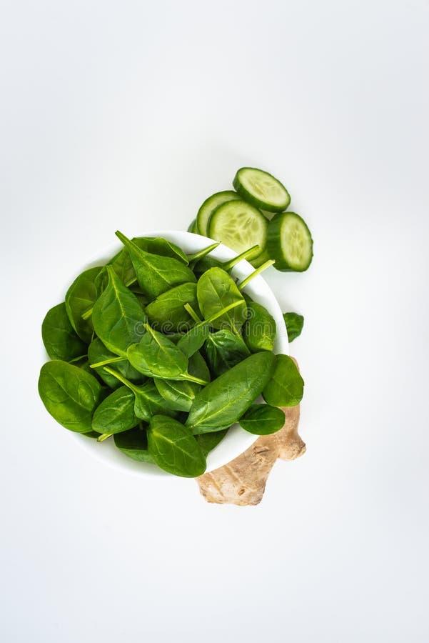 新鲜的绿色叶子菠菜、在白色背景隔绝的切片黄瓜和姜 复制文本的空间 健康 库存图片
