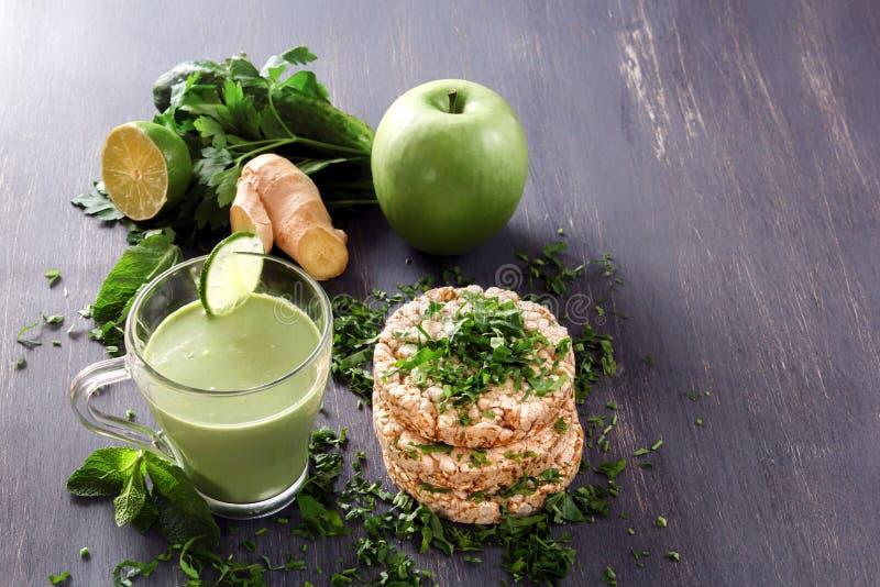 新鲜的绿色圆滑的人用荷兰芹、姜、苹果、石灰和薄菏在一块玻璃在一张黑木桌上在喘气的麦子蛋糕旁边 库存图片