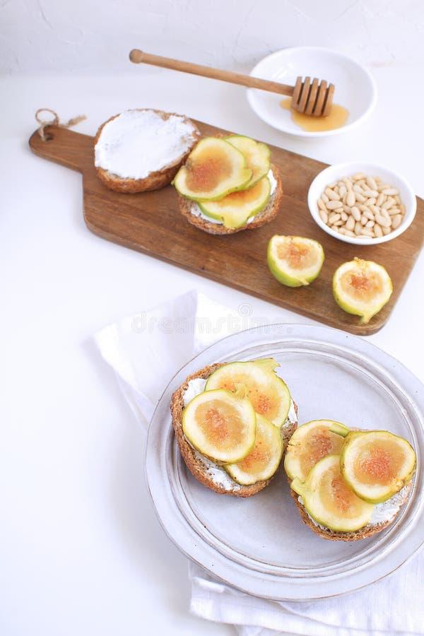 新鲜的绿色无花果木cutboard,瓷板材,整粒面包 免版税库存照片