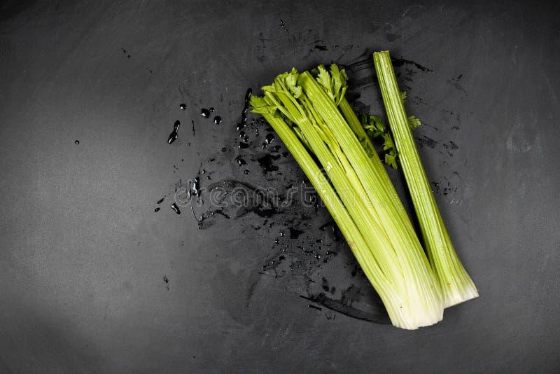 新鲜的绿色有机芹菜和水在黑背景 免版税图库摄影