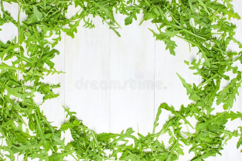 新鲜的绿色芝麻菜叶子框架,在白色木土气背景顶视图舱内甲板的rucola沙拉放置与文本的地方 火箭 免版税库存照片