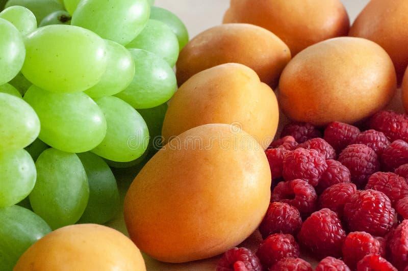 新鲜的绿色葡萄、莓和成熟杏子在木质地表面顶部 r 免版税库存图片