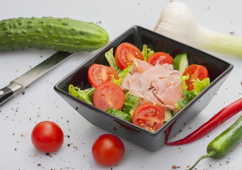 新鲜的绿色黄瓜、红色蕃茄和在白色背景隔绝的蔬菜沙拉叶子 菜沙拉的成份 库存照片