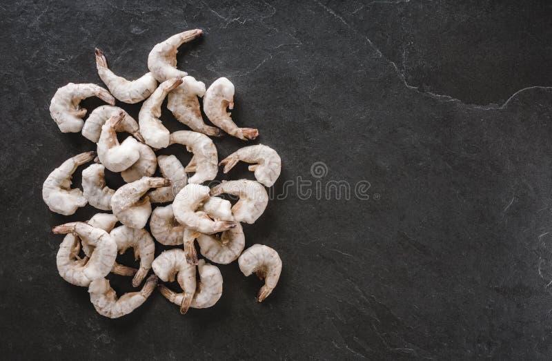 新鲜的老虎虾或大虾与冰在板岩石头背景 海鲜,顶视图 免版税库存照片