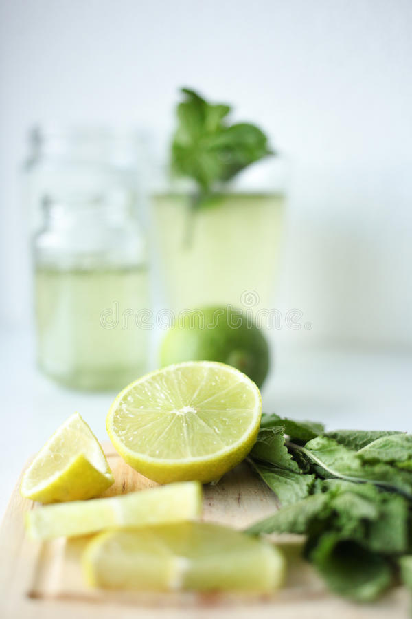 新鲜的自创柠檬水用柠檬、石灰和薄菏在一块放置在桌的玻璃在白色背景和成份 图库摄影