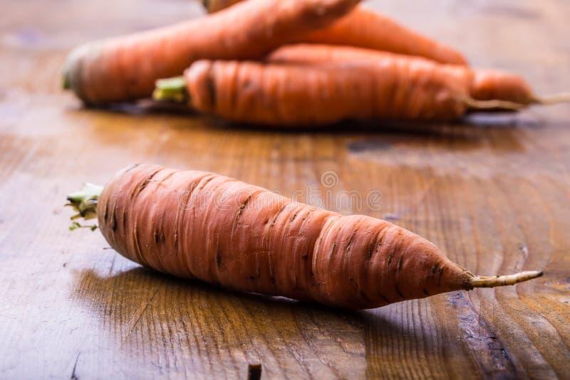 新鲜的自创红萝卜在一张木桌上疏松 免版税图库摄影