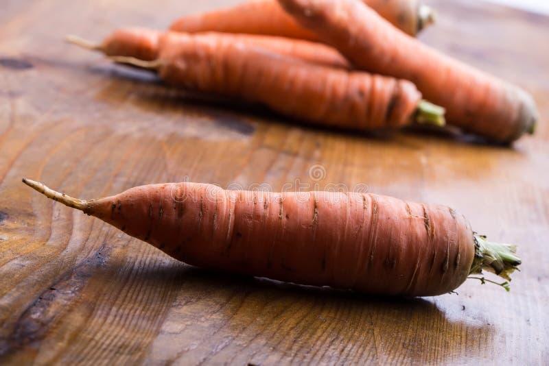 新鲜的自创红萝卜在一张木桌上疏松 图库摄影
