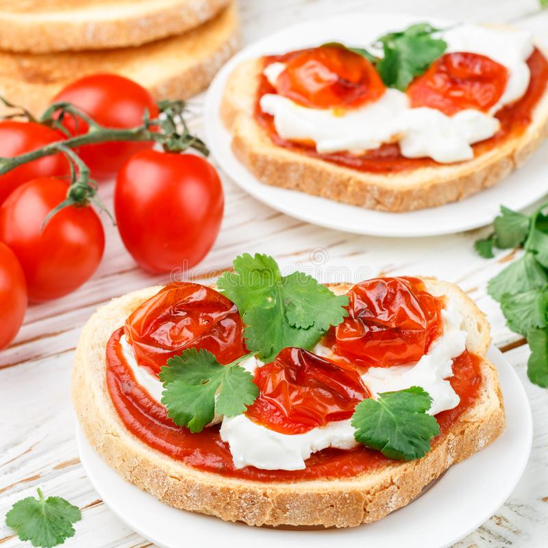 新鲜的自创酥脆bruschetta用被烘烤的蕃茄樱桃,奶油奶酪乳清干酪、红色调味汁和荷兰芹香菜正方形pictu 库存照片