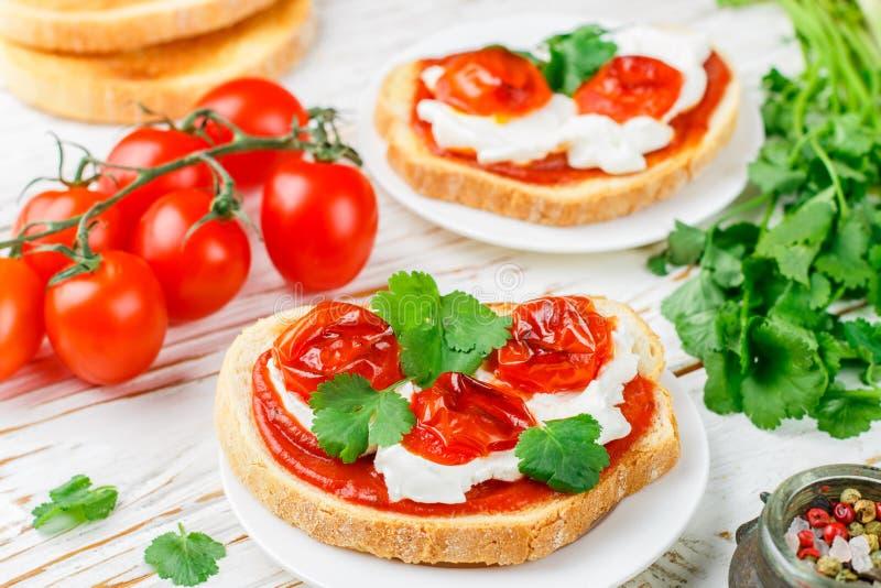 新鲜的自创酥脆bruschetta用被烘烤的蕃茄樱桃,奶油奶酪乳清干酪、红色调味汁和荷兰芹香菜 图库摄影