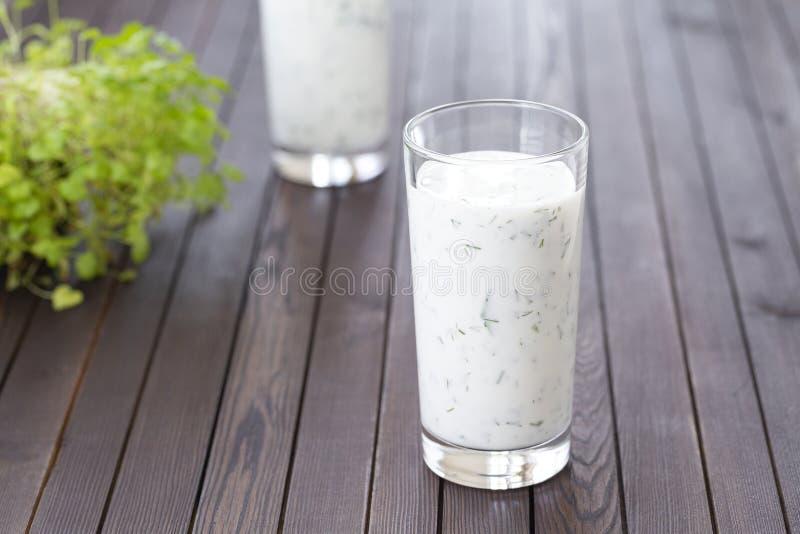 新鲜的自创酸奶牛乳气酒,在玻璃的ayran用草本 Ayran,自创酸奶饮料用草本和黄瓜-健康夏天 库存照片
