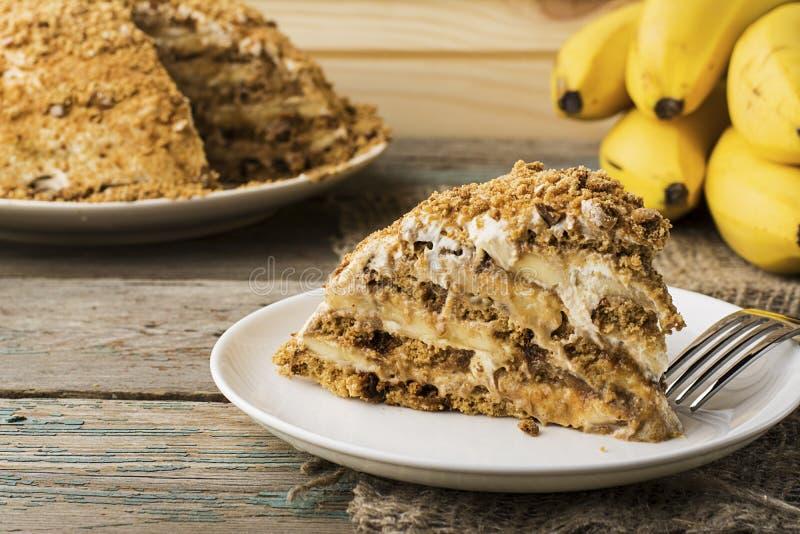新鲜的自创香蕉吹蛋糕用饼干,酸性稀奶油,香蕉切片,在简单的灰色木背景的蜂蜜 库存图片