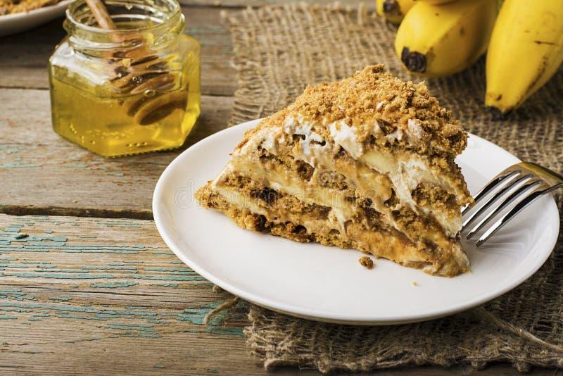 新鲜的自创香蕉吹蛋糕用饼干,酸性稀奶油,香蕉切片,在简单的灰色木背景的蜂蜜 免版税库存照片