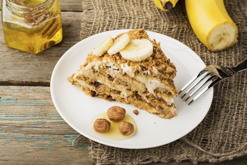 新鲜的自创香蕉吹蛋糕用饼干,酸性稀奶油,香蕉切片,在简单的灰色木背景的蜂蜜 免版税库存图片