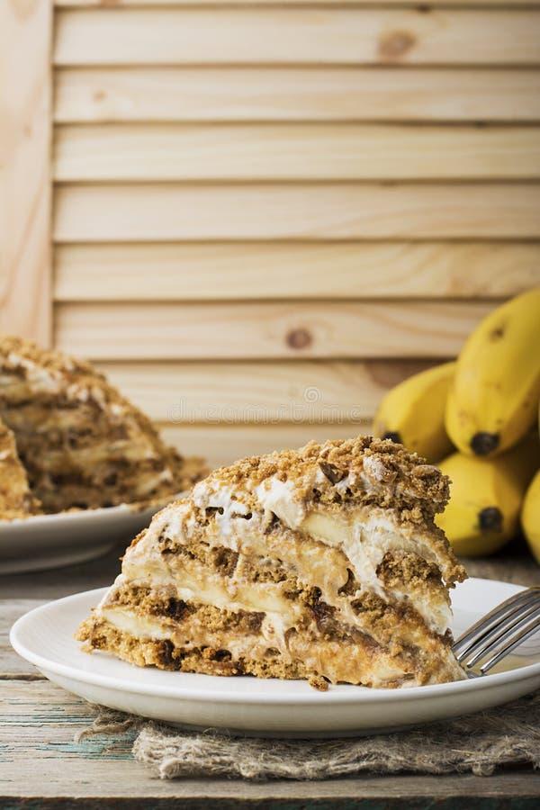 新鲜的自创香蕉吹蛋糕用饼干,酸性稀奶油,香蕉切片,在简单的灰色木背景的蜂蜜 库存照片