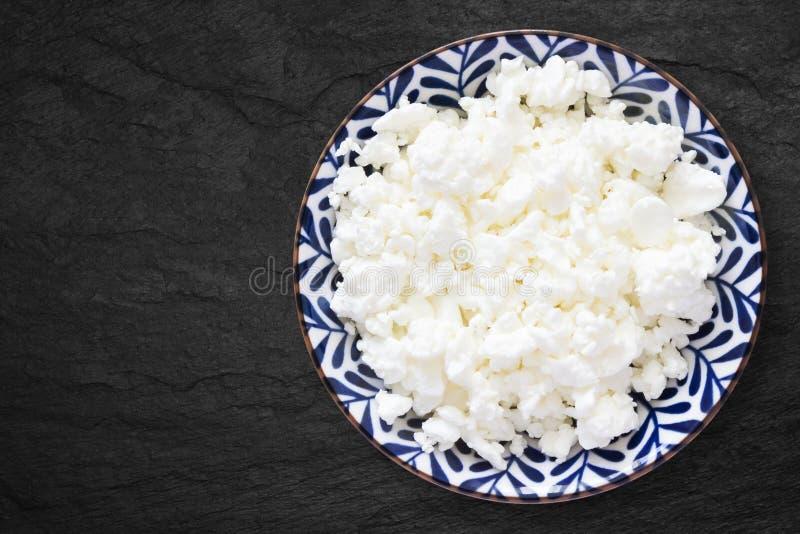 新鲜的自然酸奶干酪一张顶上的照片在一个花卉陶瓷碗的在黑石书桌上 有机eco健康膳食, 免版税库存图片