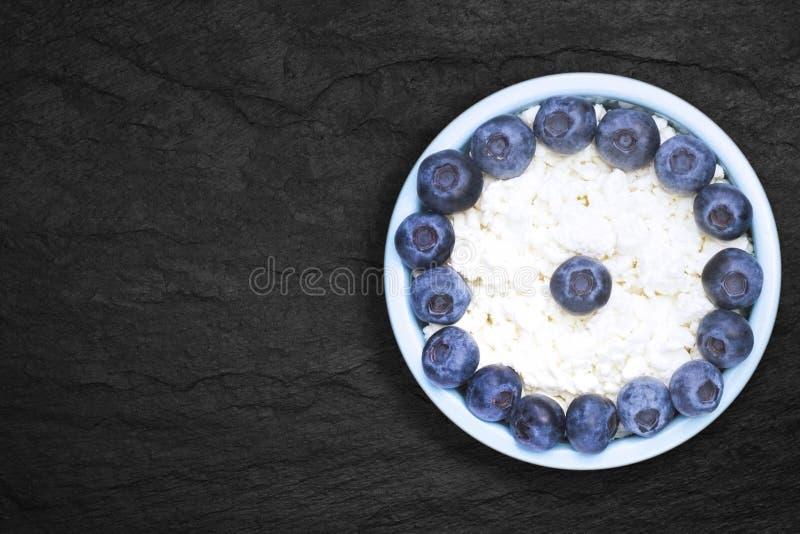 新鲜的自然酸奶干酪一张顶上的照片用在一个蓝色陶瓷碗的蓝莓在黑石板材 有机eco 库存照片