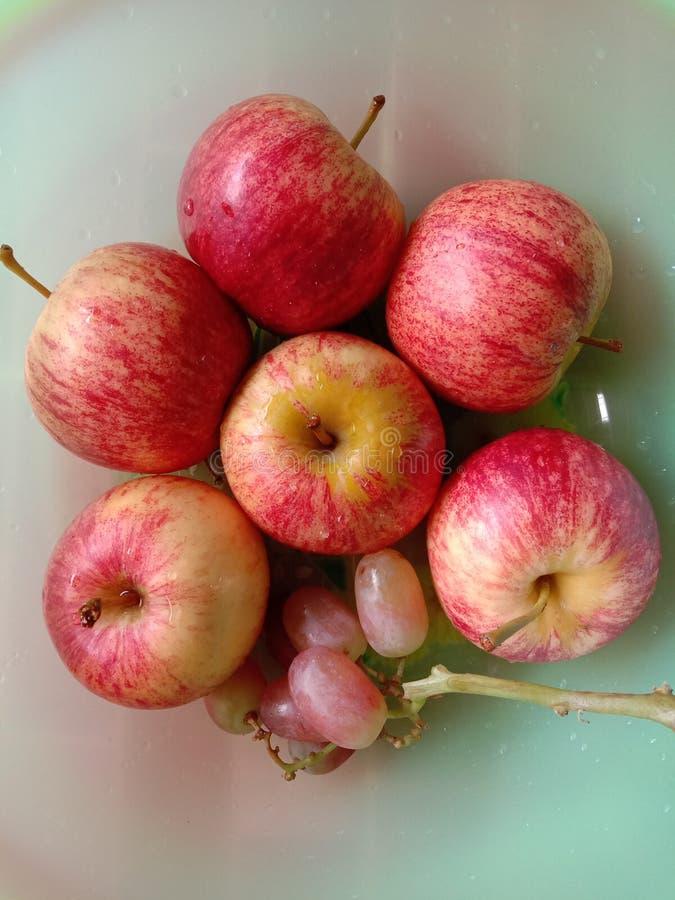 新鲜的苹果和葡萄在浅绿色的背景 免版税库存图片