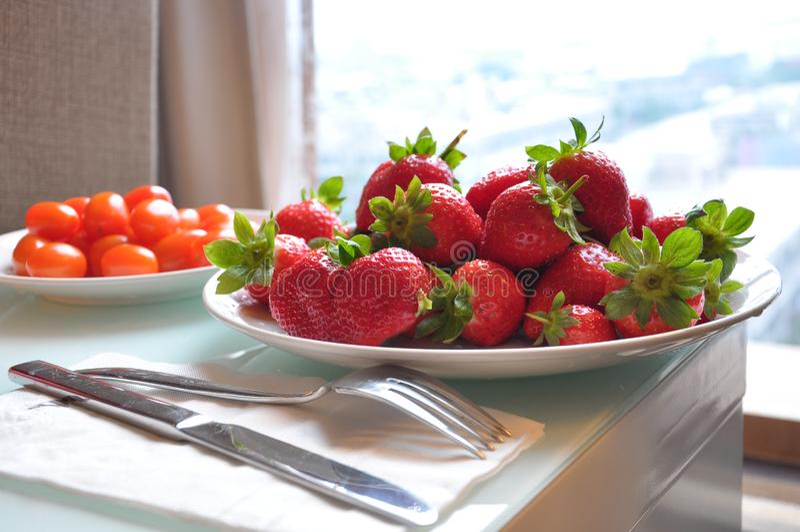 新鲜的草莓和西红柿板材在桌上在窗口附近 库存照片