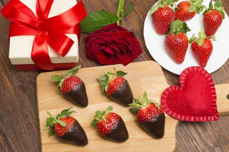 新鲜的草莓在黑暗的巧克力、礼物和心脏浸洗了在木背景 日s华伦泰 免版税库存图片